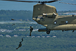 Military Parachutists jumping from the CH-47 Chinook helicopters, while UH-60 Blackhawk provided photo flights